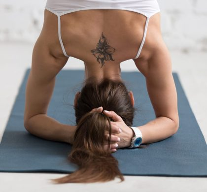 Beautiful young woman with flower tattoo on her back working out indoors. Doing yoga exercise on blue mat. Supported headstand posture. Salamba sirsasana. Rear view. Close-up