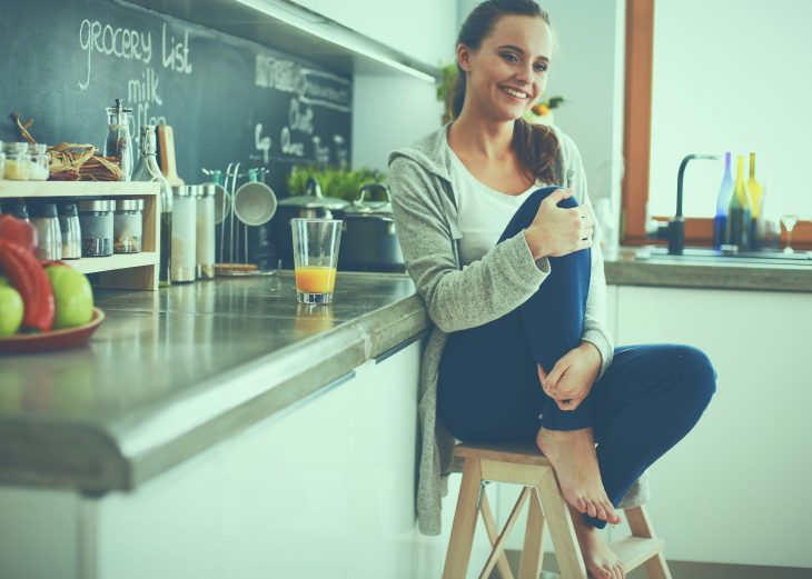 bigstock-Young-woman-sitting-a-table-in-174613897