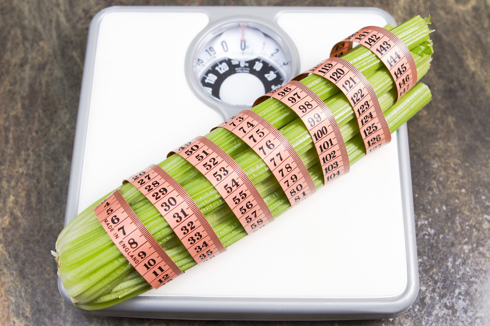 Zero calorie celery Raw celery wrapped in a tape measure on a set of scales