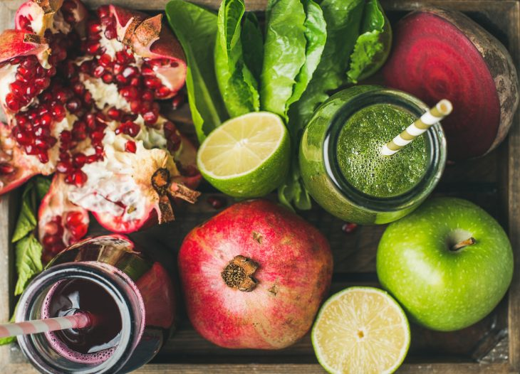 Close-up of green and purple fresh juices with fruit, greens, vegetables in wooden tray, top view, selective focus. Detox, dieting, clean eating, vegetarian, vegan, fitness, healthy lifestyle concept