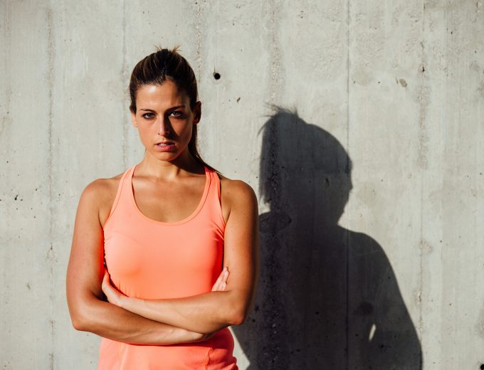 Confident serious sportswoman portrait. Sporty beautiful woman looking intensely. Motivation and sport concept.