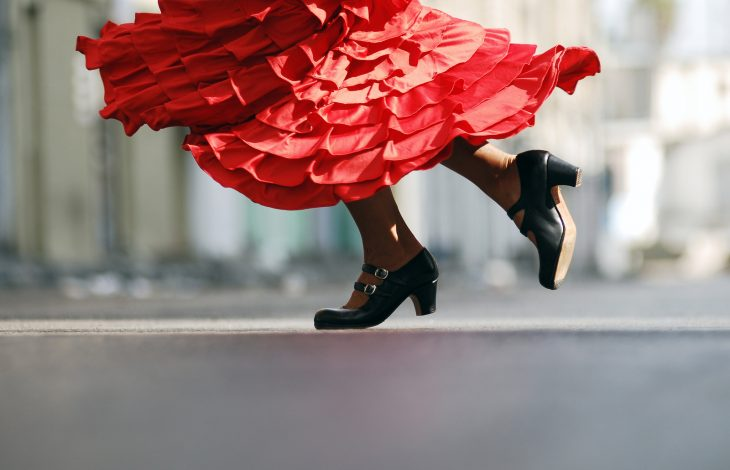 Female Flamenco dancer's legs, wearing a traditional red dress